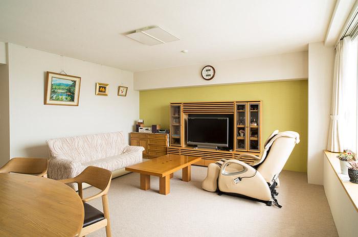 キッチンで用いた暖かみのあるリーフグリーン色をリビングの壁1面にも採用。空間の一体感をカラーリングでも演出している