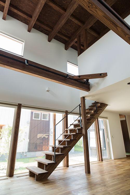 8畳超の吹き抜けを設け、明るく開放的なリビングに。照明は梁の側面に分散配置。それぞれを上下に向けることにより、夜間のリビングをさまざまな表情に演出できる