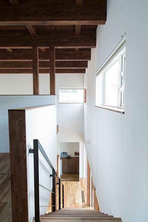 2階から見下ろす階段スペース。吹き抜け上部の窓によって明るい屋内空間に