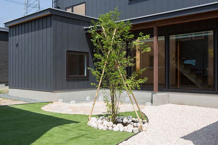 「子どもを遊ばせたり、バーベキューなどができる空間がほしかった」とAさんが切望した中庭。石張りと人工芝を組み合わせ、今後はウッドデッキも設置予定で、多彩な表情を持つ屋外プライベート空間に