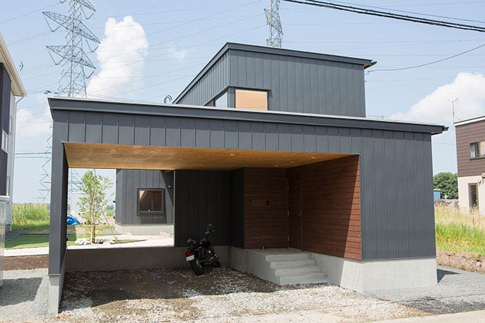 ガルバリウム鋼板と道産トドマツ羽目板でまとめたシックな外観。カーポートの奥に中庭が見える