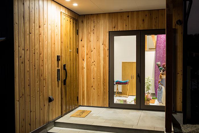 玄関スペースはドアを含めて杉板張りに。ガラス戸の奥に土間が見える