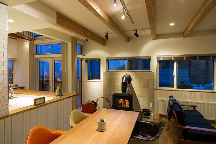 リビングから見たダイニング・キッチン。眺望サイドには窓が連なり、道産カラマツの梁が空間のアクセントに