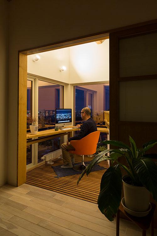 眺望のよい2階の角に設けた書斎スペース。2面に取った大きな窓からは、都市と自然が織りなすパノラマを存分に楽しめる。スリット床にすることで、真下に位置するダイニングの明るさもアップ