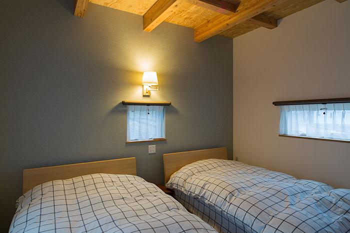 主寝室の天井は、構造材のカラマツを見せて暖かな雰囲気に仕上げている