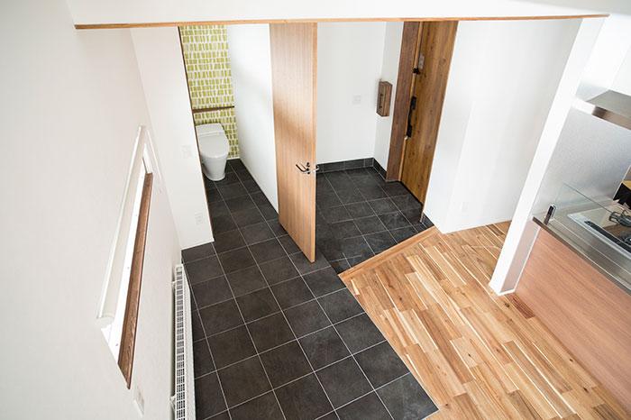 玄関やトイレのスペースを斜めに区切ることによって動きのある空間構成に