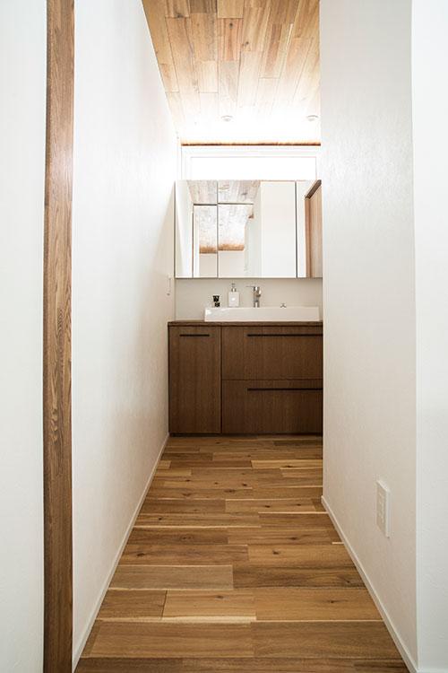 落ち着きのある造作家具でまとめられたユーティリティ。上部に採光窓が設けられ、ほどよく明るい空間に