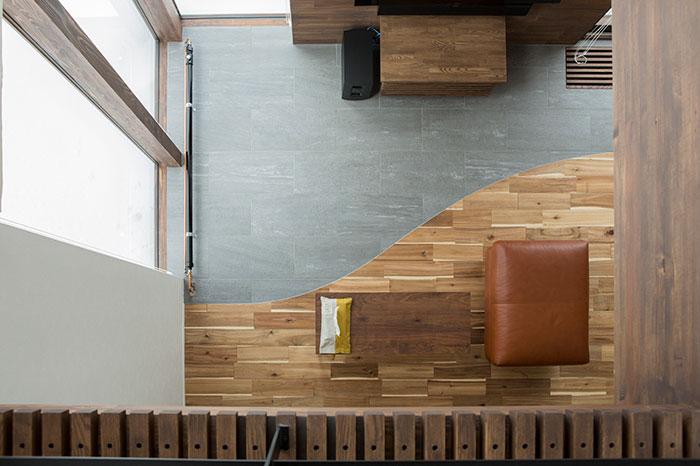表情豊かなアカシアの無垢材をメインに、窓側の土間へとつないでデザインに変化をもたせたリビングの床