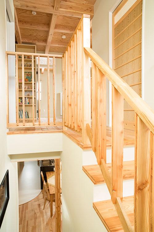 床に天井、手すりまで、ウッドで構成された暖かみのある2階フリースペース。本棚は造作。「造作家具はサイズも空間にフィットするので、地震が来ても倒れづらいという安心感があります」とSさん