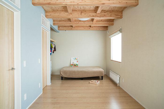 ライトブルーの壁が印象的な子ども部屋。将来的には2部屋に間仕切できるつくり