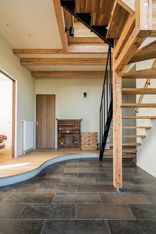 土間と無垢フローリングとの境界は曲線になっており、美しく柔らかな雰囲気に。フローリングから土間を跨いで階段を上ることができる