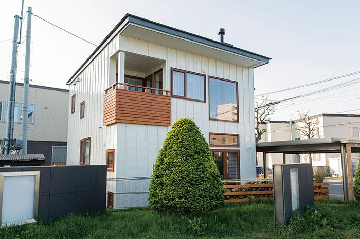 オフホワイトのガルバリウム鋼板にウッドを組み合わせた外観。庭にはご主人お手製の薪棚も