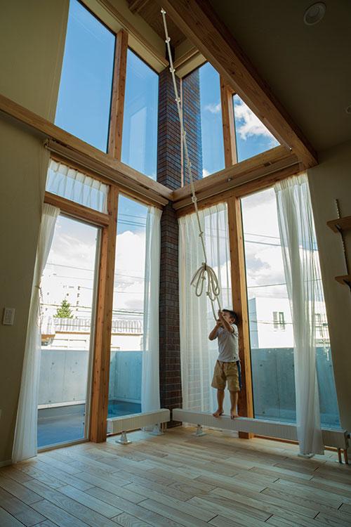 吹き抜けには2面のガラスカーテンウォールが配され、都市部の密集した住宅地でありながらも明るく快適なリビングを実現。吹き抜け上部の梁からお子さんが遊べるロープも吊り下げられている