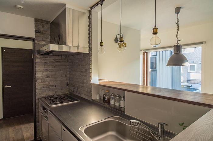 キッチンは対面式ながら、中の様子が見えすぎないように適度な高さの間仕切りを配置。その高さを生かして調味料などを置くスペースも設けられている。ガスレンジ周りは、ダークグレーのレンガ壁を採用