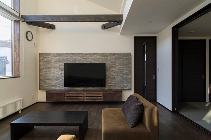 リビングのテレビ台は造作で、左側の扉が玄関外のポスト口と直結。リビングにいながら郵便物や新聞などを取り出せるしくみに。テレビ背後のタイル部分と壁面の間には間接照明が埋め込まれている