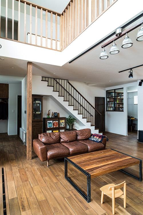 リビングの一部は吹き抜けに。1階の床には、ほどよく主張する木目が魅力的なアカシア無垢材を採用。以前から使用していたというソファやテーブルも、落ち着いたトーンの空間になじんでいる