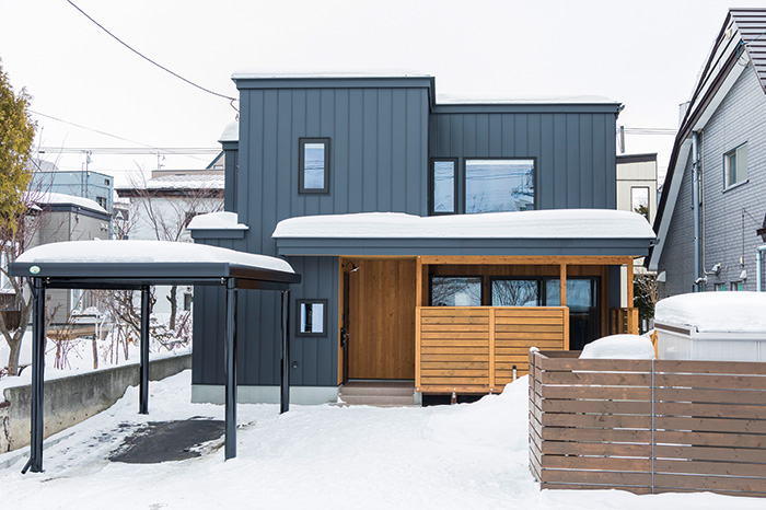黒のガルバリウム鋼板に、一部カラマツの板張りで構成した外観。ウッドデッキの塀は、家の前を通る人の視線を遮りながら、遠景は室内に取り込める高さに調整されている