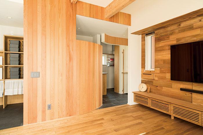リビングと廊下を仕切る木壁にはレッドシダーを用いた。上部を開け、曲面にすることで開放感を出している