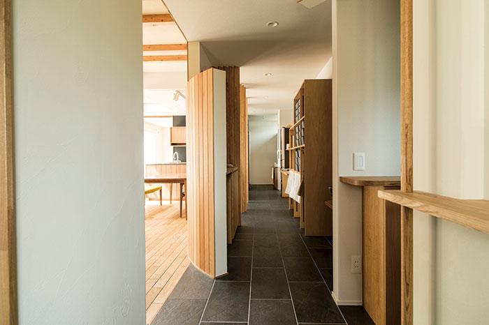 玄関から見た廊下。ダークグレーのタイル床にすることで、LDKとは異なる空間の役割を明確にしている。木壁の曲面の裏側はマグネット対応のホワイトボードになっており、家族の掲示板として活用されている