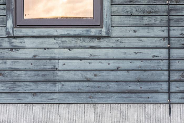 1階部分の外壁の様子。ダークグレーで塗装された板張りは、時を経て味わいのあるトーンに変化してきた