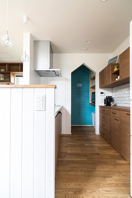 キッチンの腰壁は、白塗りの木壁にしてリゾート感を上品に演出。キッチン奥にはパントリーを配置。主張しすぎない場所に色鮮やかな壁紙をセレクトし、遊び心のある空間に。このターコイズブルーの壁紙は1階トイレにも使用