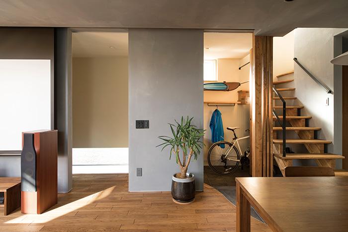 玄関土間からリビング・ダイニングへのアクセスは2ヵ所から。玄関ドアに近い写真左はお客様用、右はご家族用で使い分け。右から入ると、ダイニングの床もタイル張りとなっており、空間のつながりを感じられる