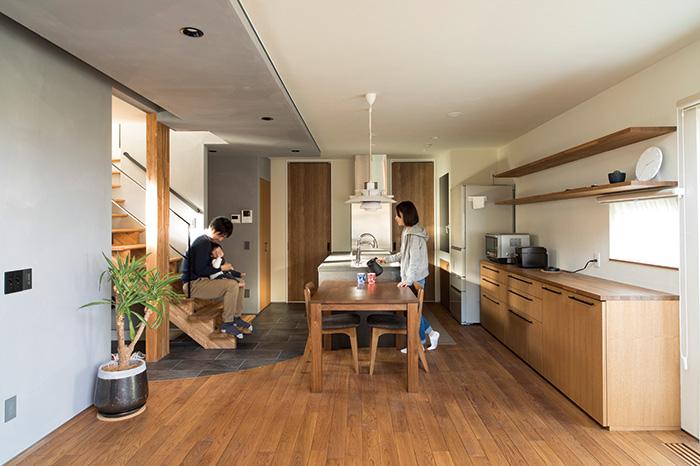 リビングから見たダイニング・キッチン。参考とした企画型のプランよりもキッチンを奥へ移動してリビング側にゆとりをもたせている。階段の配置もリビングから見えるようにすることで2階とのつながりを強めている
