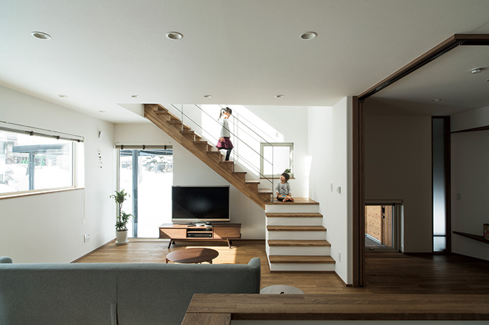 暮らしの中で家族が顔を合わせやすい空間づくりを意識し、リビングに階段を設けた。吹き抜けからの採光も考慮されている