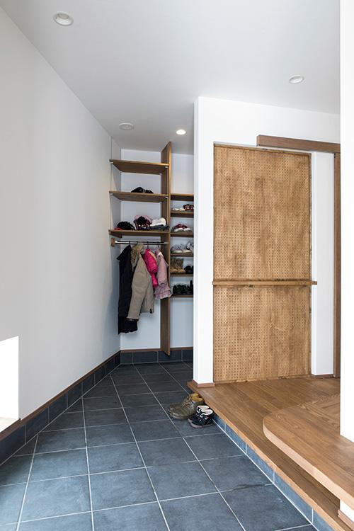 広々とした玄関土間。右手前は、お子さんの靴を履かせたり、買い物袋などを置くのに便利なベンチ。土間は右奥に伸び、シューズクローク、さらにドッグケージのあるスペースへとつながっている