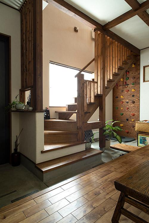 玄関ドアから写真奥に見えるボルダリング練習用のウォールまで続く土間。手前にある廊下から1階洋室へアクセスできる。土間を跨いで階段を上ると2階リビングへ