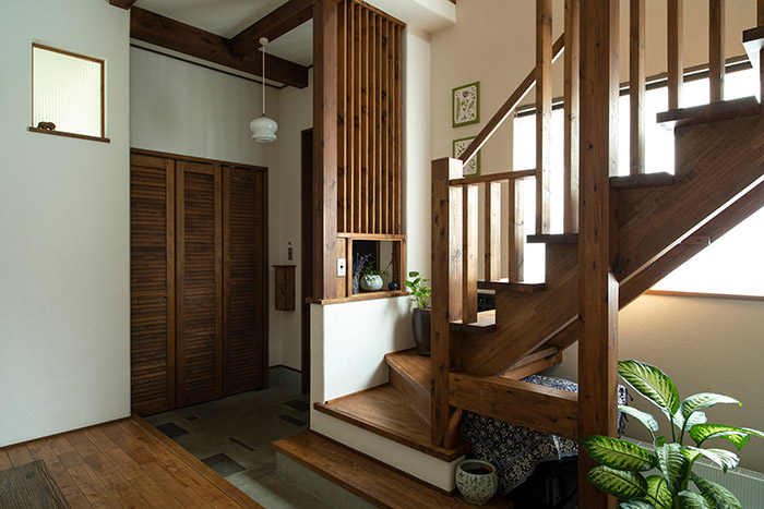 木の質感にこだわった階段は、10年を経て色が深くなり、味わいが増してきた。階段下には来客のコートを掛けたり、洗ったウエットスーツなどを干せるハンガー機能も。奥に見えるのはサーフィンやスノーボードなどの道具を大量に収納できるクローク。「隣の寝室をできるだけ狭くして、クロークを広げてもらいました。すごく便利ですよ」とTさん