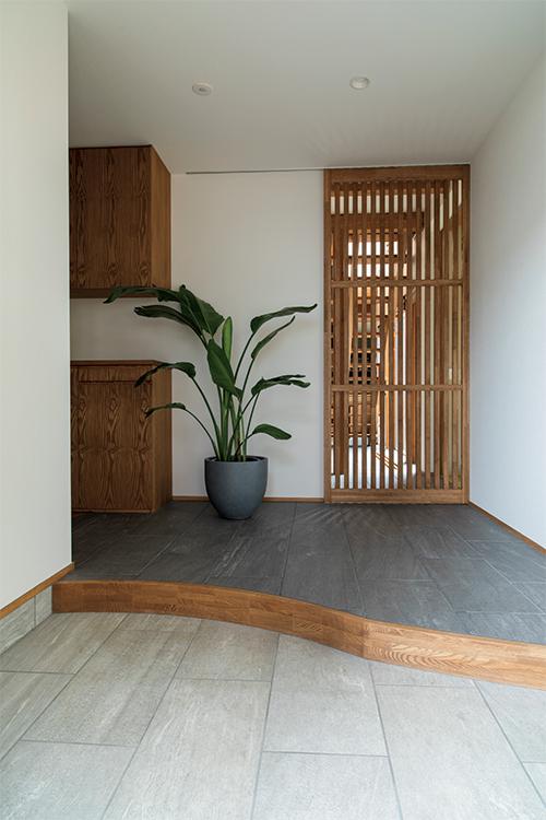 玄関は曲線を用いて、やわらかな空間に。この左側にはウォークインの広々としたシューズクローク、さらにガレージにつながるドアがある。左奥はトイレ、スリットの引き戸からリビングへ