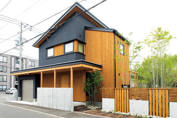 黒の塗り壁と板張りで構成された外観。木とコンクリートを組み合わせた塀は、適度に視線を遮る効果も