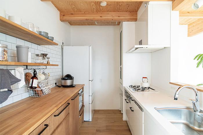 奥さんが選んだというタイルがアクセントになったキッチン。木製の収納は造作されたもの。「右奥に付けてもらった食品庫がとっても便利です」と奥さん