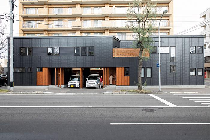 片側二車線の通り沿いに建つKさん宅。黒のガルバリウム鋼板に木板張りを組み合わせた横長の形状は存在感あり。二世帯のうちKさんご夫妻と娘さんが暮らすのは左側の部分
