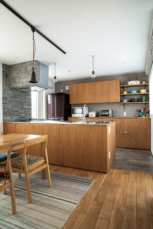 奥さんの念願だった対面キッチンは造作。ダイニング側にもたっぷり収納できる。ガスコンロまわりの壁は、清掃の手間がかからないレンガに
